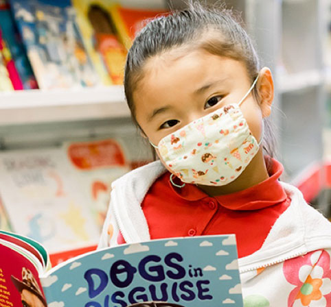 Young girl wearing a mask and reading a book