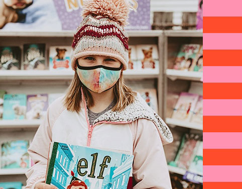 Girl wearing a mask and holding new books at a book fair