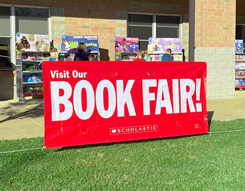 Come to Our Book Fair banner hanging in front of an outdoor Fair.